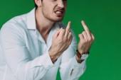 oříznutý pohled na rozzlobený muž v bílé košili zobrazující prostřední prsty na zeleném