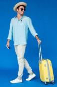 vista a tutta lunghezza del viaggiatore sorridente in cappello da safari e occhiali da sole in possesso di valigia gialla su blu