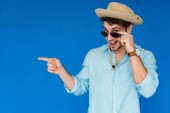 vzrušený turista v Safari klobouku a slunečních brýlích a ukazování prstem izolovaně na modré