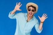 pohled na vzrušeného cestovatele v Safari klobouku a slunečních brýlích, které stojí s rukama v izolaci na modrém