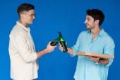 zwei lächelnde Freunde klirren Bierflaschen und schauen sich isoliert auf Blau an