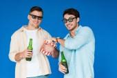 Fotografie dva usmívající se přátelé ve 3D skleničkách, držící láhve piva a popcornu izolované na modré