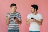 két mosolygós férfi használ okostelefonokat és nézi egymást, izolált rózsaszín
