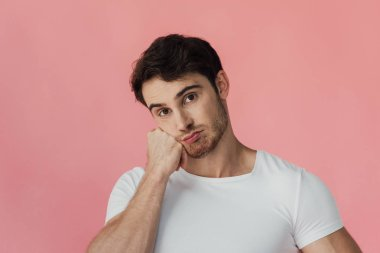 pensive muscular man in white t-shirt propping face wth fist isolated on pink