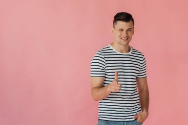 smiling man in striped t-shirt standing with hand in pocket, blinking and showing thumb up isolated on pink
