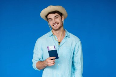 Smiling traveler in safari hat holding passport and air ticket and looking at camera isolated on blue stock vector