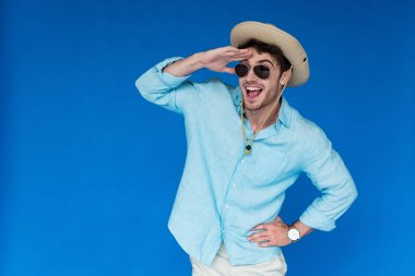 excited tourist in safari hat and sunglasses laughing and looking in distance isolated on blue