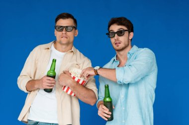 two friends in 3d glasses holding bottles of beer and popcorn isolated on blue
