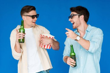 two smiling friends in 3d glasses holding bottles of beer and popcorn isolated on blue