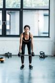 mladá žena ve sportovním oblečení při cvičení s barbellem v tělocvičně