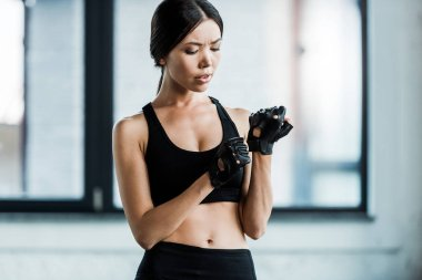 Attractive young woman wearing black gloves in gym stock vector