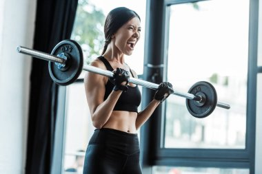 emotional young woman in sportswear working out with barbell in gym