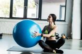 šťastná dívka drží modrý fitness Ball, když sedí na fitness rohoži