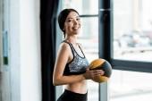 Glückliche Frau hält gelben Ball in der Hand und lächelt im Fitnessstudio