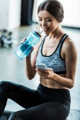 Photo happy sportswoman using smartphone and sport bottle with water