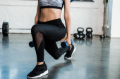 vista cropped di sportiva facendo esercizio squat con manubri
