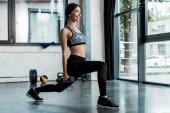 sportiva felice facendo esercizio squat con manubri