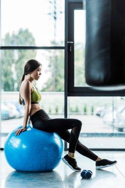 Selective focus of pretty girl sitting on blue fitness ball near dumbbells stock vector