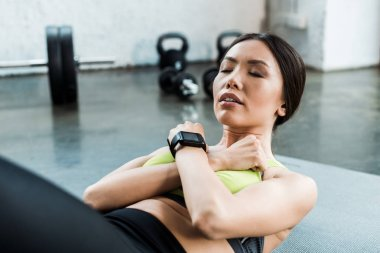 attractive young woman with closed eyes doing do abs on fitness mat