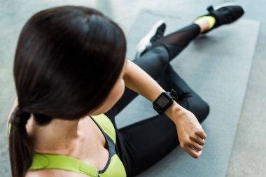 selective focus of woman looking at fitness watch while sitting on fitness mat