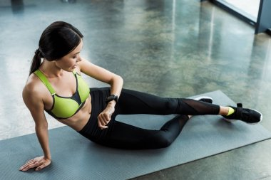 attractive woman looking at fitness watch while sitting on fitness mat