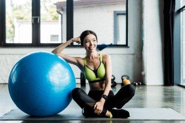 Cheerful girl sitting on fitness mat near blue fitness ball stock vector