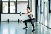 Photo happy young sportswoman holding dumbbells and doing squat exercise