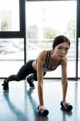 sportovní žena cvičtěnou v tělocvičně u okna