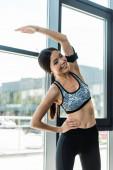šťastná a atletická žena cvičením v tělocvičně