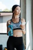 atraktivní žena používající smartphone a přidržením sportovní láhve