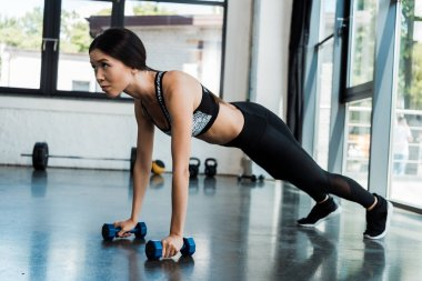 sporty girl exercising with dumbbells in gym near windows