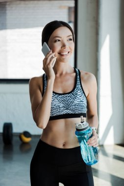 mutlu genç kadın akıllı telefon konuşuyor ve spor şişesi tutarak