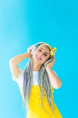 happy girl with dreadlocks in headphones looking at camera on turquoise