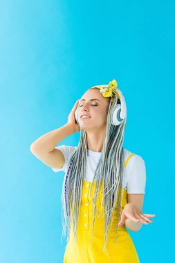 girl with dreadlocks in headphones listening music isolated on turquoise