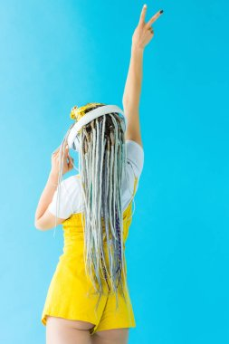 Back view of girl with dreadlocks in headphones doing Peace Sign isolated on turquoise