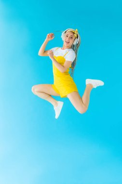 excited girl with dreadlocks in headphones jumping on turquoise