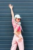 beautiful fashionable girl with dreadlocks and headphones leaning on wall