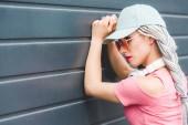 modisches Mädchen mit Dreadlocks und Kopfhörern an der Wand gelehnt