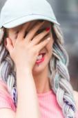 Mädchen mit Dreadlocks im Hut lacht und verdeckt das Gesicht