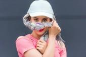 schöne stilvolle Mädchen mit Dreadlocks in Hut bedeckt Gesicht mit Haaren