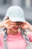 Selektiver Fokus des stilvollen Mädchens mit Dreadlocks im Hut, das die Augen mit den Händen bedeckt