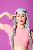 schöne stilvolle Mädchen mit Dreadlocks und Finger auf dem Kopf posiert auf lila