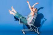 krásná stylová dívka v nákupním košíku gestikulovat na modré