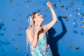 beautiful smiling stylish girl Gesturing on blue with confetti