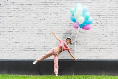 smiling girl with decorative balloons and outstretched hands posing near brick wall