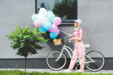 stylish girl with bicycle and balloons near building