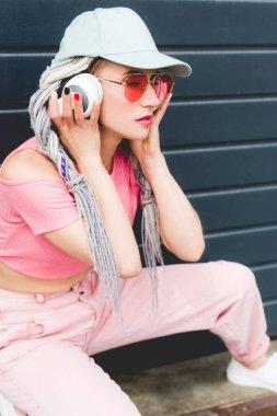 attractive stylish girl with dreadlocks and headphones posing near wall