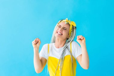 Excited girl with dreadlocks cheering with clenched fists isolated on turquoise stock vector