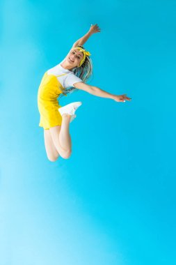 Girl with dreadlocks jumping and smiling on turquoise with copy space stock vector