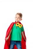 předškolní chlapec v Rudém hrdinově plášti s maskou, která hledí pryč izolovaně na bílém